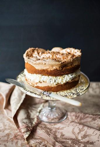 Biskuitkuchen mit Nüssen und Baiser auf Kuchenständer