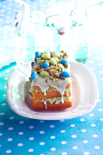 A sponge cake slice with green cream, icing sugar, seeds and sugared almonds
