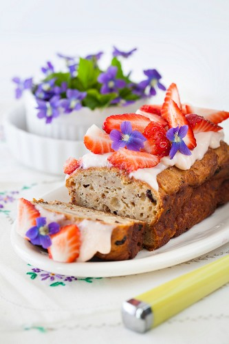 Breakfast bread with cream cheese icing, strawberries and violets