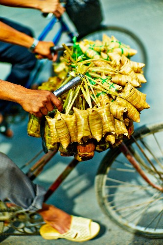 A vendor cycling with bunches of banana leaf parcels to a market in Saigon (Vietnam)