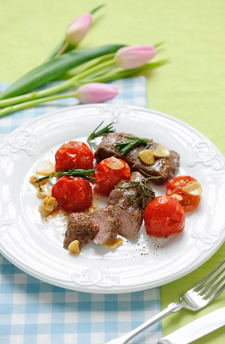 Saddle of lamb with tomatoes, garlic and rosemary