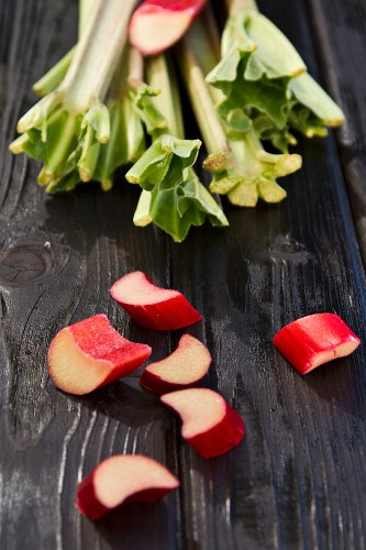 Pieces of rhubarb on a wooden surface with rhubarb stalks in the background
