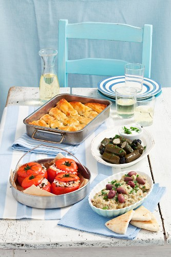 Various Greek appetisers: dolmadakia, tomatoes stuffed with rice, spanakopita, aubergine dip with olives