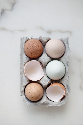 Whole eggs and egg shells in an egg box (seen from above)