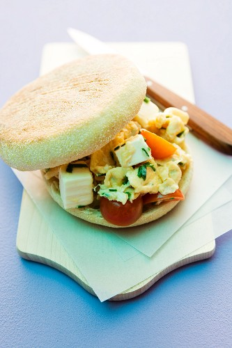 Scrambled eggs, feta and tomatoes in an English muffin