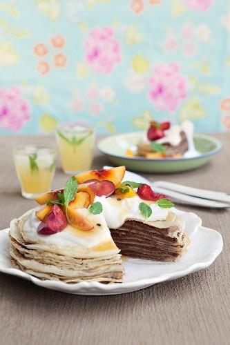 Pancake cake with chocolate cream, salted caramel, peaches, plums and grenadilla