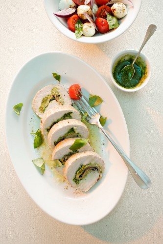 Turkey roulade with ham and a herb pesto served with a tomato and mozzarella salad