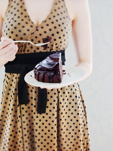 A woman in a spotted dress eating a slice of chocolate cake