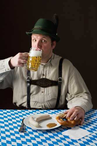 A stereotypical German man wearing lederhosen and eating white sausage with a beer