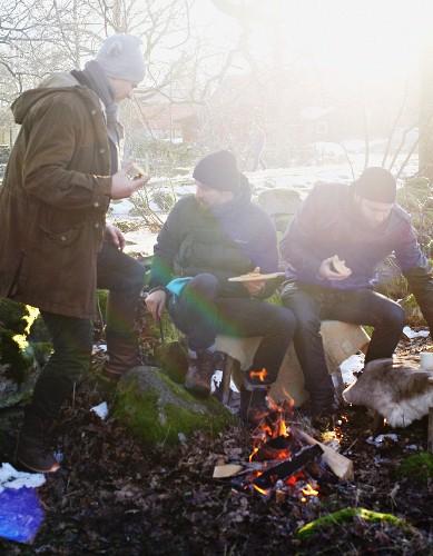 Freunde essen Pizza am Lagerfeuer im Winter