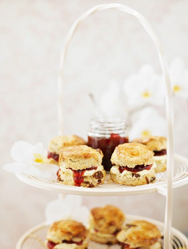 Scones with cream and strawberry jam on a white metal cake stand