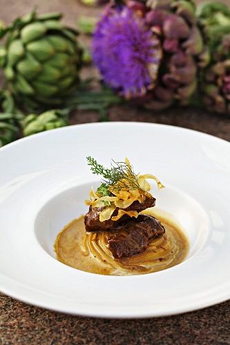 Braised pork cheeks with artichoke crisps and Jerusalem artichoke cream