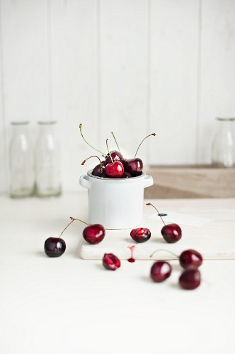 Cherries in a white porcelain pot and in front of it