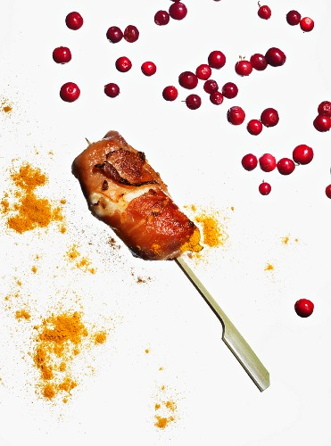 Chicken skewer with bacon, curry and pink peppercorns