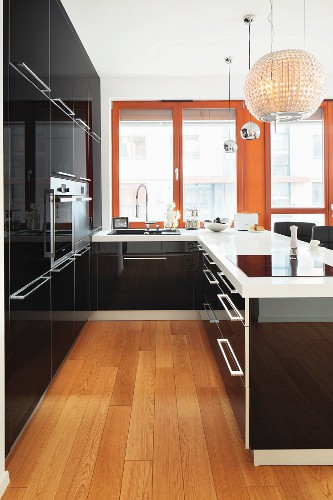 A designer kitchen with shiny black cupboards and elegant pendant lamps above a bar counter