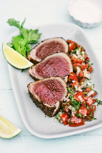 Tuna fish steaks with a sesame seed crust served with fennel seeds, coriander and a tomato and onion salsa