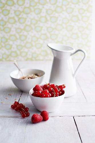 Raspberries, redcurrants, muesli and a jug of milk