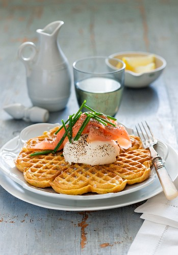 A spicy curried waffle topped with a dollop of cream and ham