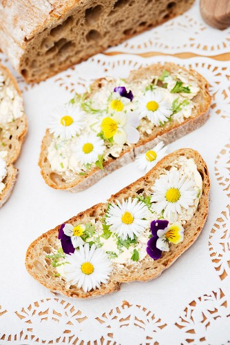 Slices of bread topped with daisies and tufted pansies