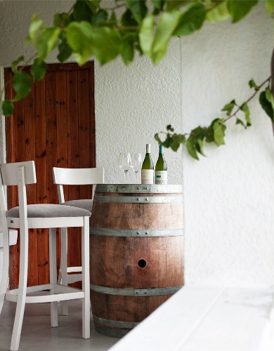 Bottles of white wine with glasses on a barrel in a wine tasting room