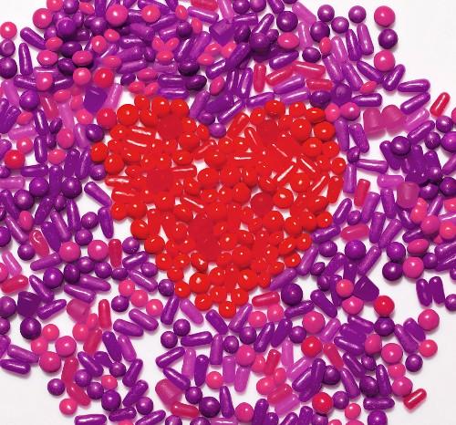 Violette Bonbons, in der Mitte Herz aus roten Bonbons geformt