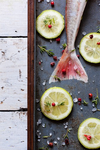 A raw fish, lemon slices, thyme, pink pepper and coarse sea salt
