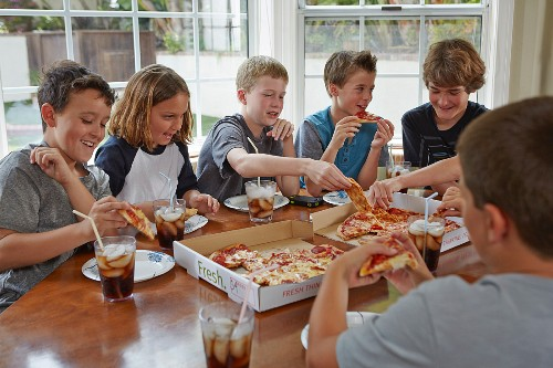 Group of boys eating pizza from boxes at a kitchen table