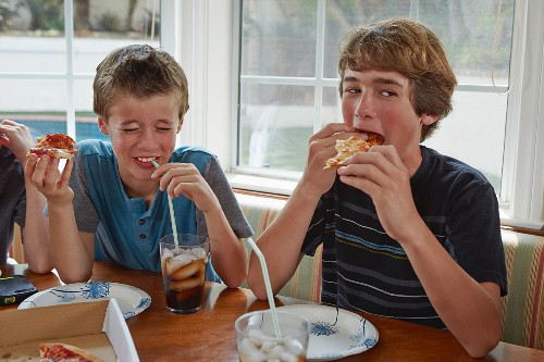 Boys eating pizza and drinking cola in a kitchen