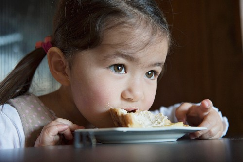 A little girl eating cake directly off the plate