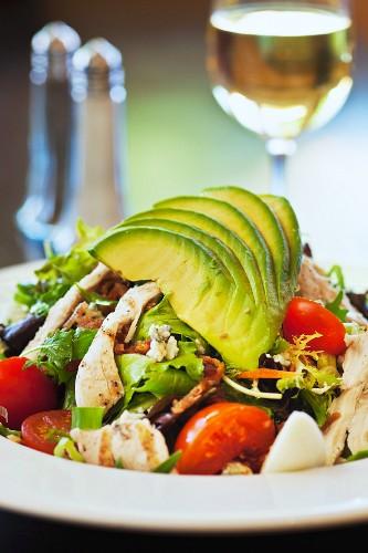 Cobb Salad mit Avocado, Tomaten, Speck und Hähnchen vor einem Glas Wein