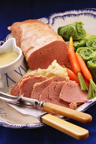Traditional corned beef on a platter with mashed potatoes and vegetables