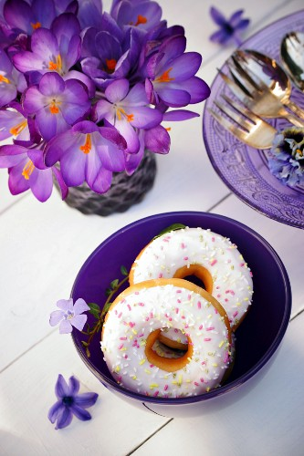 Doughnuts in a purple bowl decorated with purple flowers and a bunch of crocuses