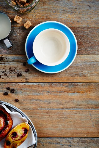 An empty coffee cup, sugar cubes and baked goods