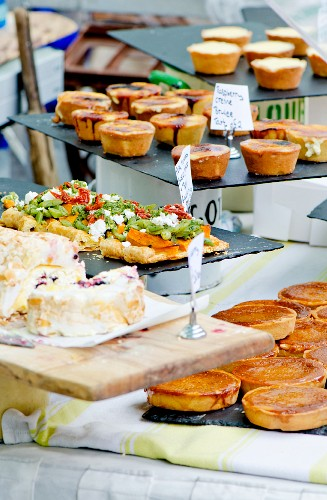 A market stand selling baked goods featuring syrup cakes and vegetable pizzas (England)