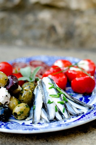 An antipasti platter with marinated anchovies, olives and pimientos filled with ricotta (Italy)