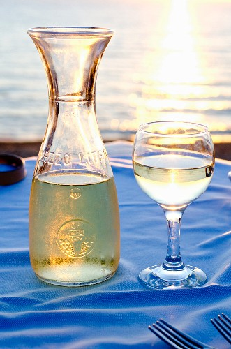A carafe and a glass of white wine on a restaurant table with a sea view