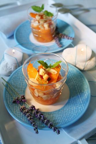Vin Santo Pfirsiche mit gerösteten Mandelblättchen, Kekswürfeln und Minzeblättchen