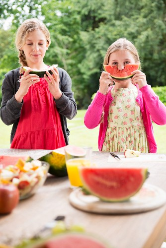 Two sisters on a terrace eating and holding watermelon wedges