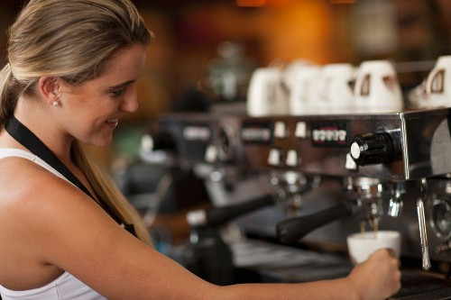A young waitress preparing coffee in a cafe