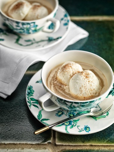 Egg white dumplings in tea and vanilla cream with ground cinnamon