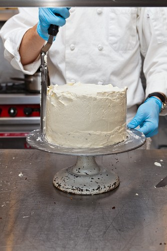 A confectioner decorating a cake