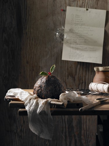 A Christmas pudding decorated with holly on a rustic wooden table with a hand-written recipe pinned to the wall behind