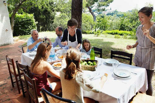 A family eating together in a summery garden