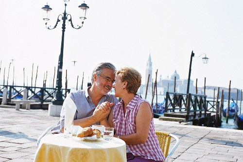 An older couple sitting at a pavement cafe, Venice, Veneto, Italy