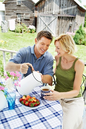 A couple having coffee on a patio with a farm house in the background