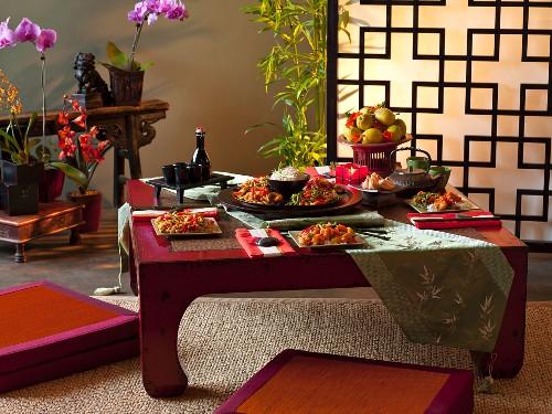 Gedeckter Tisch mit asiatischen Gerichten in asiatischem Ambiente
