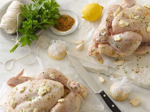 Ready to roast chickens with butter, lemons, parsley, garlic and spices