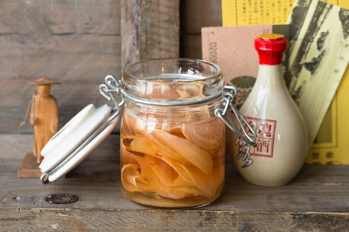 Sweet-and-sour pickled ginger in a flip-top jar on a wooden shelf