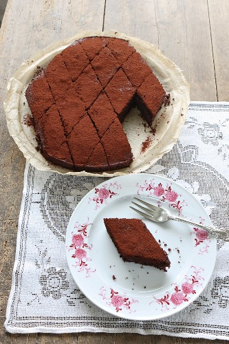 A chocolate cake cut into diamond shaped slices on a wooden table with a lace cloth