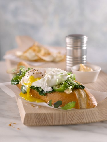 Poached egg on a slice of French bread topped with spinach, pepper and cress with aioli, potato crisps and a salt shaker in the background